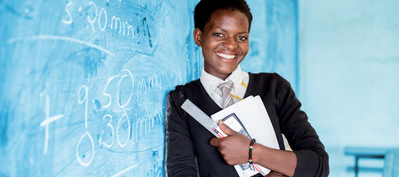 A smiling adolescent girl, holding school supplies and a calculator, leans against the blackboard during a class, in Kamulanga Secondary School in Lusaka, the capital.