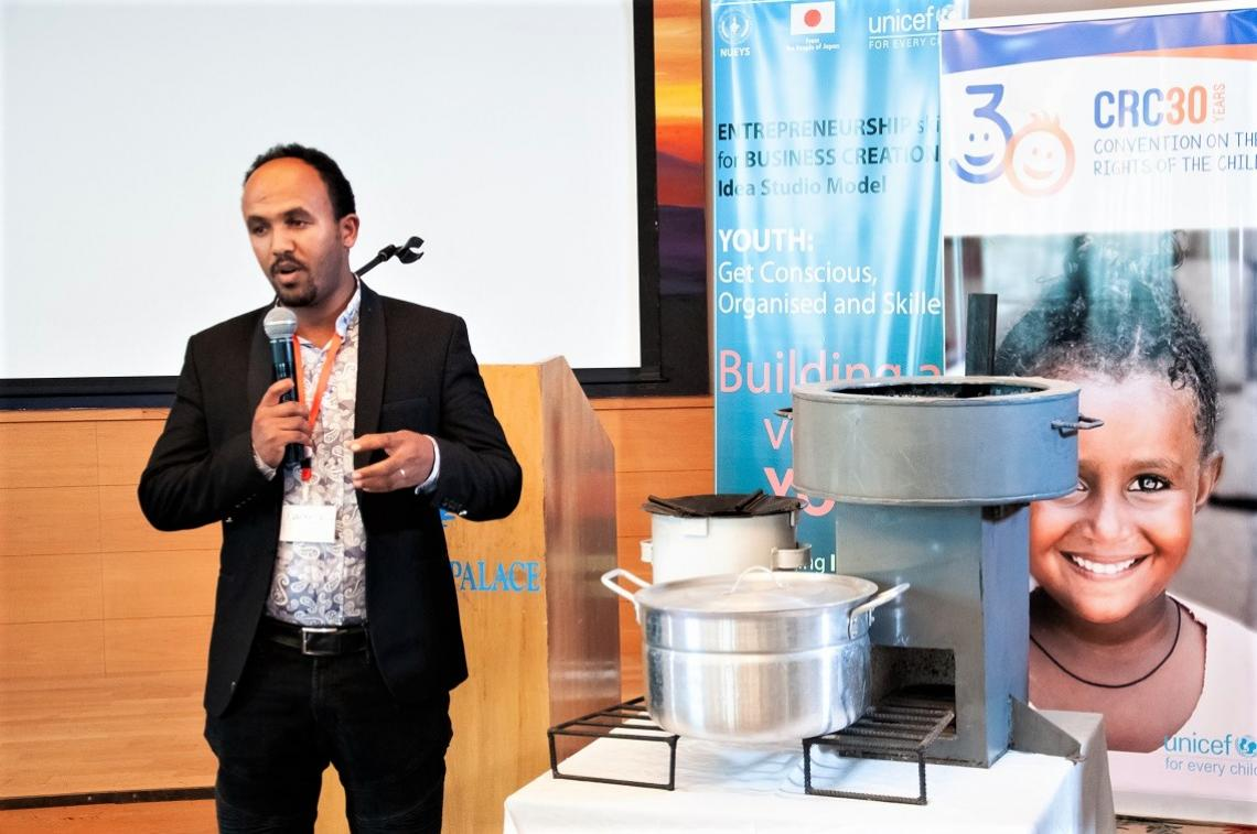 A man speaks into a microphone, standing next to a stove display.