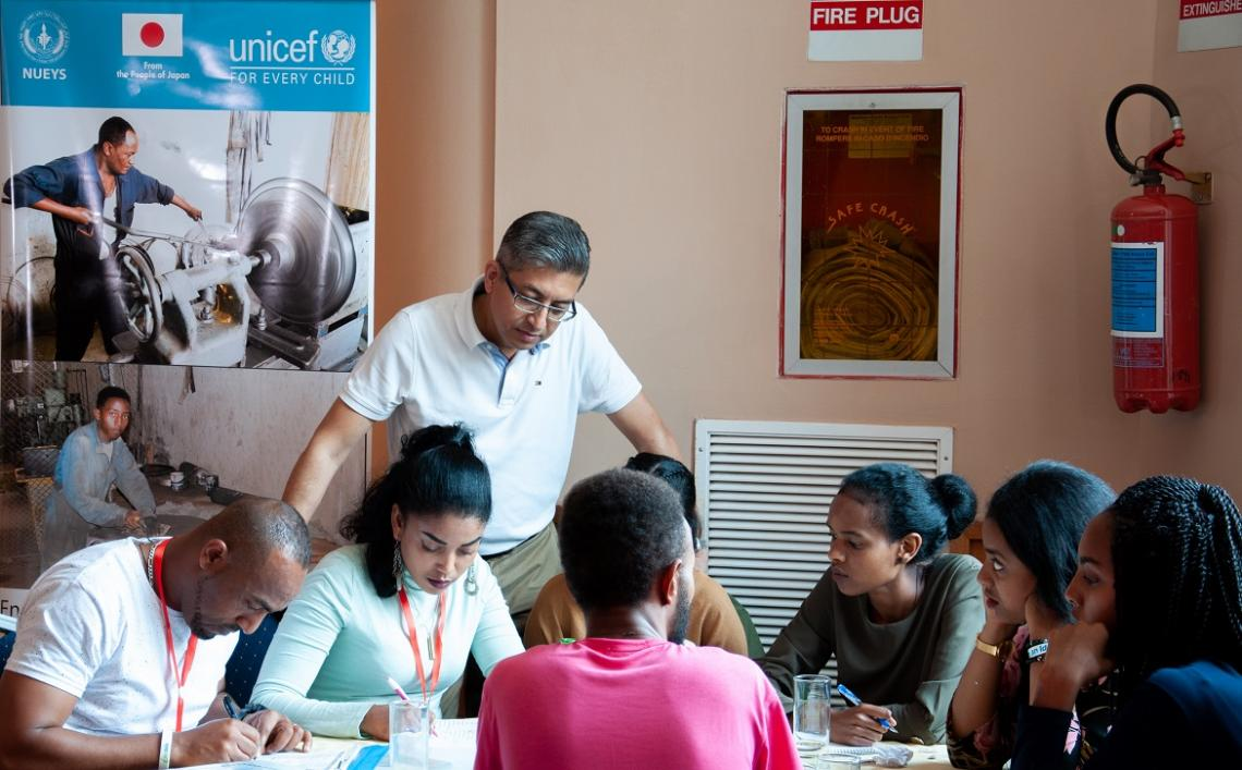 Professor Shrestha looks over students at a table.