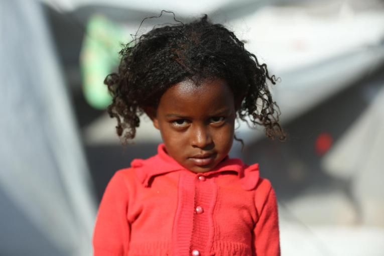 A young girl gazes intently at the camera at a refugee camp in eastern Sudan