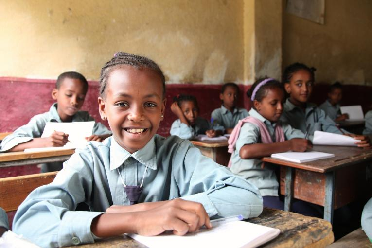 A girl smiles from a desk in a school classroom