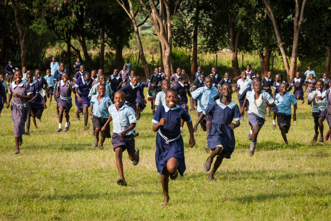 Children run through a field at a school in Kenya