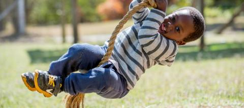 A boy is swinging on a role swing, smiling for the camera.