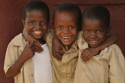Three boys embrace, smiling for the camera