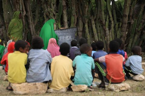 Children attend class under cactus tree and sitting on stone stools in Hagajin Libah.