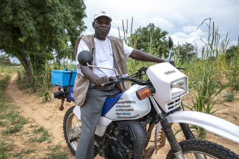 The main civil registrar coming to pick up the birth declarations to the village on his motorbike.