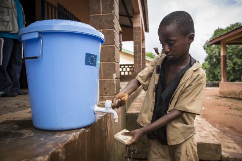 Sekouba, 10, washes his hands with soap before entering his classroom as a preventative measure to stop the spread of Ebola at Ecole Primaire Forécariah Centre, Guinea. In this school, hand-washing facilities have been supplied by UNICEF with the support of the EU.