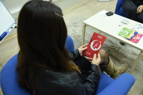 A teenage girl reads a brochure at the Judicial Interview Room in İzmir, Turkey.