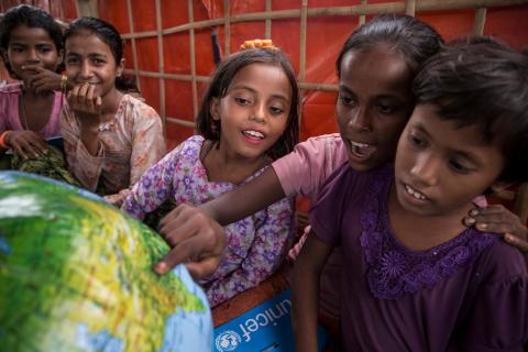 Students look at an inflatable globe, part of the educational supplies contained in a School-in-a-Box, at a new Transitional Learning Centre in the Uchiprang refugee camp, near Cox's Bazar, Bangladesh, Saturday 21 October 2017.