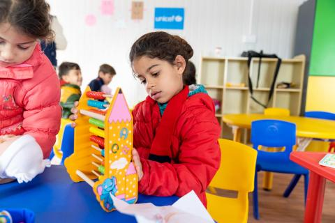 A child plays with an abacus at her KG class in Za'atari Refugee Camp