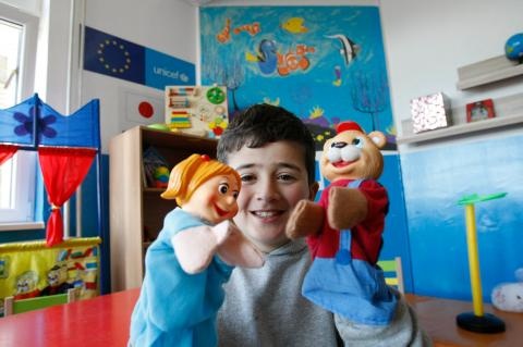 Syrian refugee child playing with puppets in Serbia