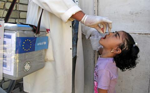 A health worker administers a dose of oral polio vaccine to an child in Baghdad's Sadr City, Iraq.