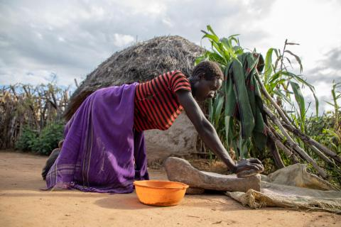 Agnes Lokiru, one of the project beneficiaries, prepares a meal for her family.
