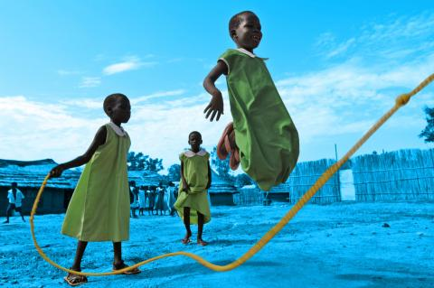 Girls laugh as they play skip rope during playtime in Sudan
