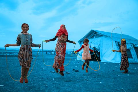 On 1 October 2018 at the Junaina makeshift camp in northern rural Idlib, in the Syrian Arab Republic, girls jump rope outside of a tent school where a total of 350 children between the ages of 7 and 14 are able to go back to learning.