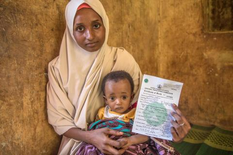 Aisha Usman holds their Birth certificates of her twin children issued at the office of a traditional scribe in Gwadangaji, Nigeria.