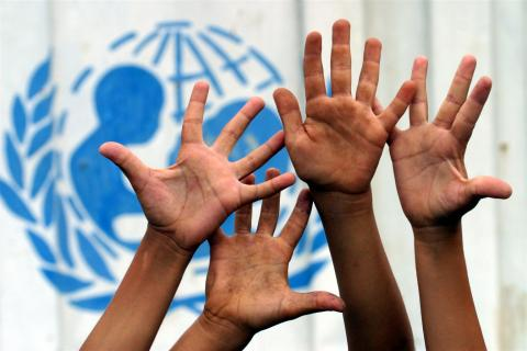 Children's hands are raised high in front of a portion of the UNICEF logo painted on the side of a shipping container