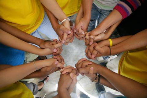Youth leaders stand in a circle, holding hands, to symbolize the slogan 'We can do it together'.