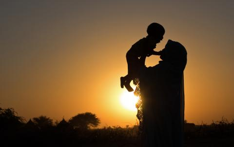 Mother and child play against a backdrop of the setting sun