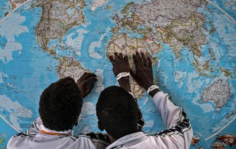 Two boys point to the location of The Gambia on a wall map.