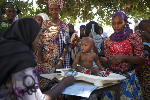 Child receives routine health check at outreach clinic in The Gambia