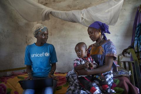 UNICEF staff gathers information from a mother