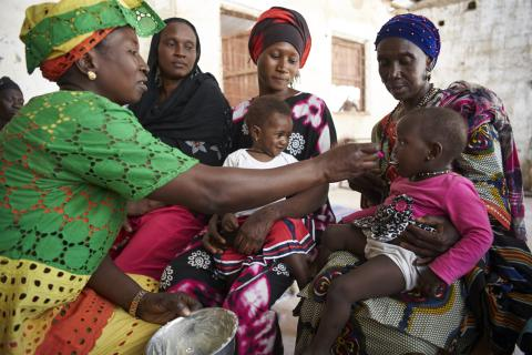 Baby is being fed porridge made from locally-available foods, while other women look on
