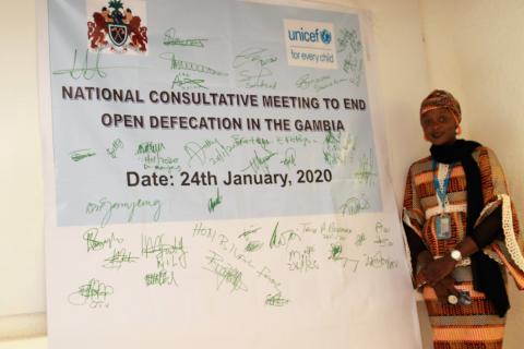 UNICEF staff stands beside a banner bearing the pledges of government and partners to end open defecation