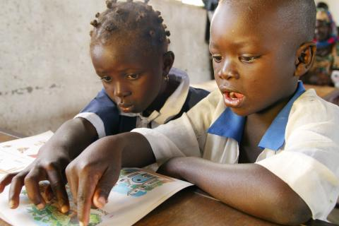 Boy and girl read from a book in primary school