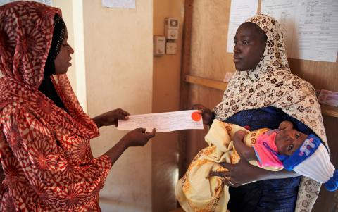 Public health worker hands over a birth certificate to a mother