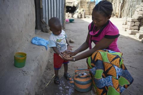 A lady washes the hands of a child with soap and water