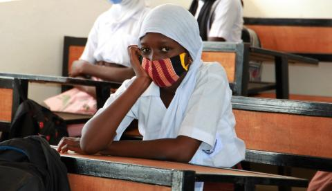 A girl stares at the camera during a UNICEF visit to her school in Mansakonko
