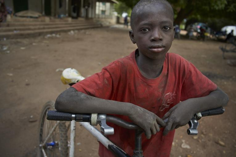 A child leans on a bike