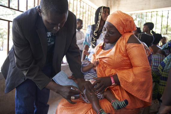 Mother winces as child receives immunization at an outreach clinic