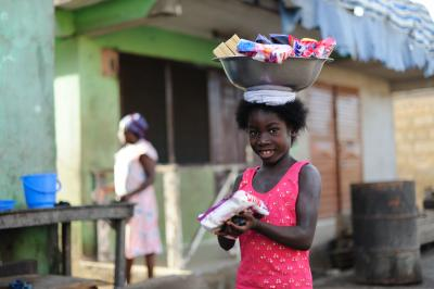 A girl selling soaps and washing powder out of a basin carried on her head in the historic slaving town of Elmina in the Central Region of Ghana on 20 May 2012.