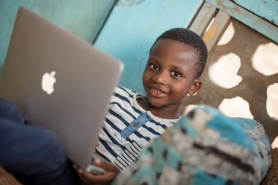 Jude Tetteh, 6 years, plays a game on his father's laptop after school in Darkuman, Accra on 8 October 2018.