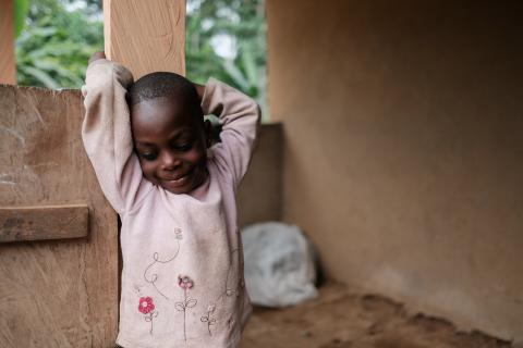 A young girl smiles in front of her house