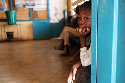A young boy hides behind the door at a health center