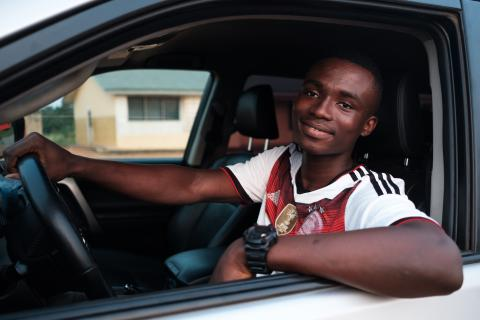 A young man behind the wheel of a car