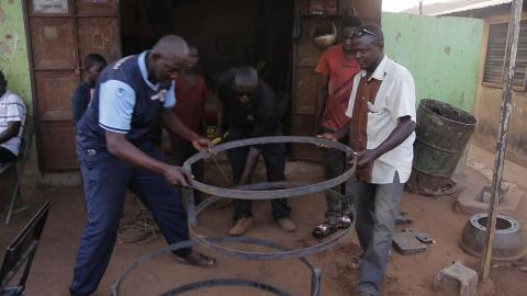 A group of men inspect the fabrication of a frame to build substructures of toilets