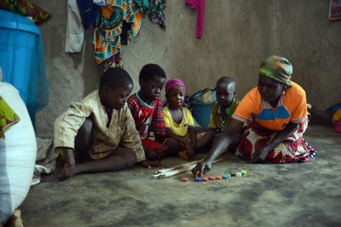 A mother teaches her children with household items and the radio