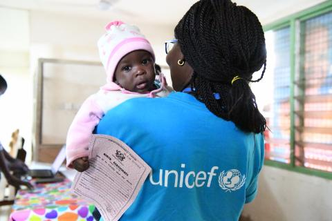 A little holds his birth certificate as he is carried by a UNICEF official