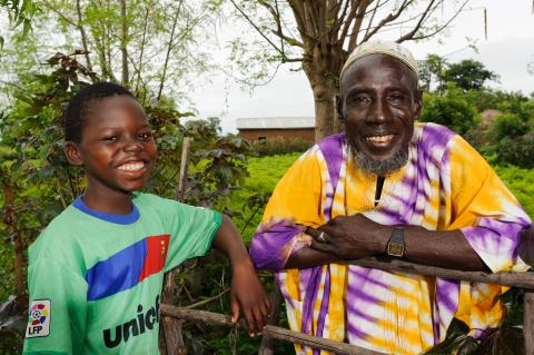 A young boy with his father in their community in the Northern Region