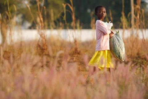 A girl carries a plastic bag as she walks to school in Tanzui, Ghana on Thursday November 11, 2010.