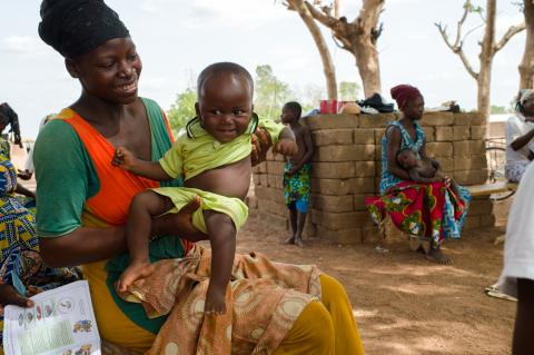 Woman with baby waiting to be registered for social protection support