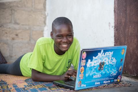 A young girl smiles as she uses her laptop for homework