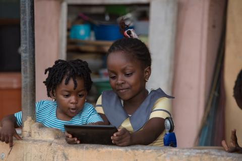 Christina Amartefio (6), and her sister Christabel (2) playing with their mother's tablet on 12 October 2018.