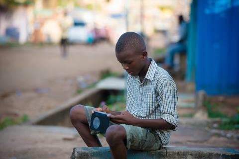 Christian Afari, 13yrs, plays a game by the side of the street on 12 October 2018.