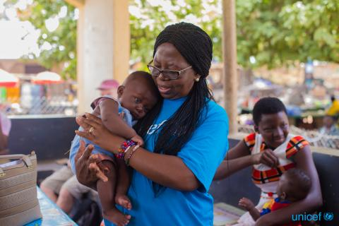 UNICEF staff holding a baby