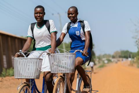 Two girls riding their bikes from school